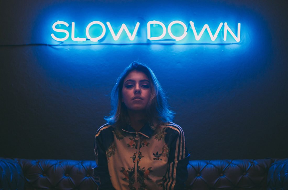 Girl with slow down neon sign