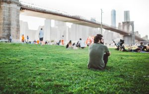 Man sitting by bridge and contemplating