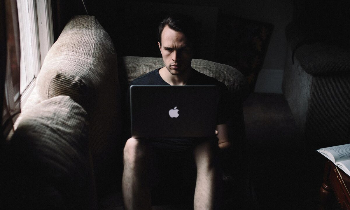Man using laptop on his knees in a dark room