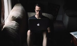 Man using laptop on his knees in a dark room