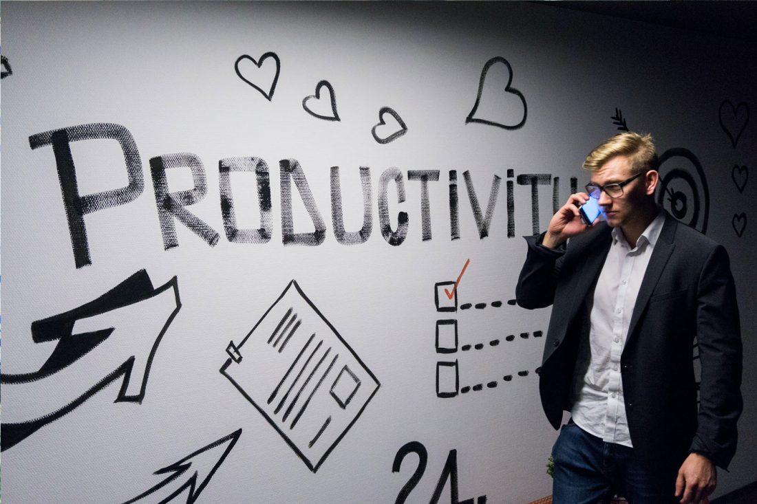 Man talking on phone by productivity mural