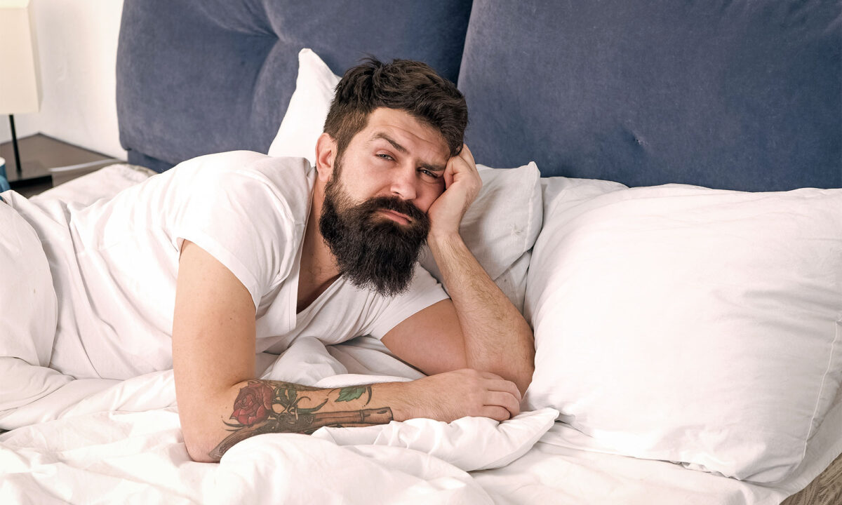 Man lying in bed looking at camera questioningly